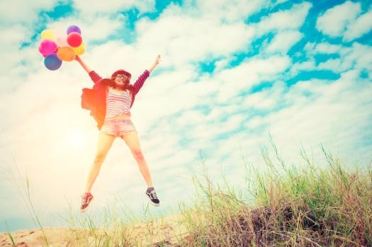 Chica saltando feliz con unos globos
